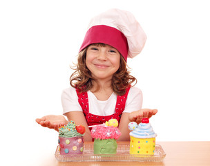 happy little girl cook with sweet cupcakes