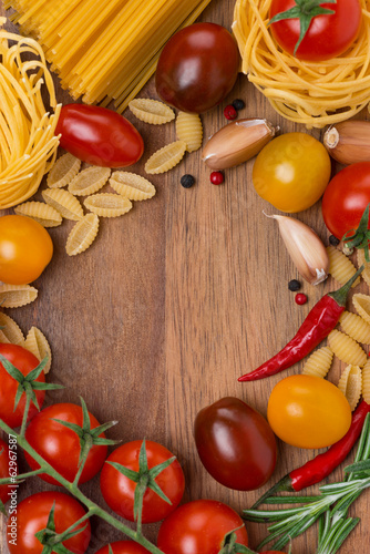 pasta, spices and cherry tomatoes on a wooden board, concept