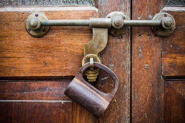 Closeup old door with lock in grungy style and wood texture.