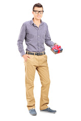 Full length portrait of a man holding a present