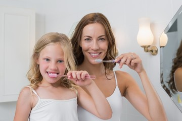 Portrait up of mother and daughter brushing teeth