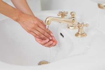 Close-up side view of washing hands at washbasin