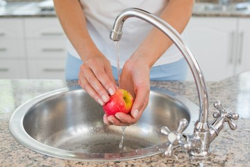 Mid section of hands washing apple at washbasin
