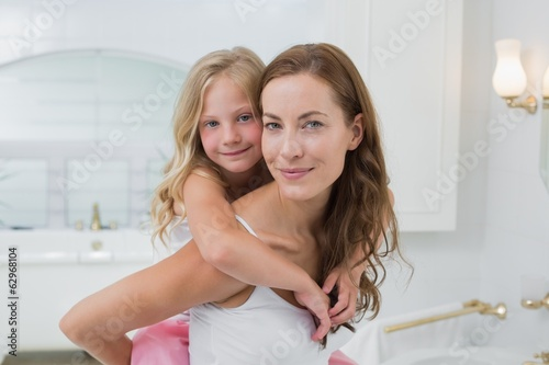 Woman carrying young girl in the house