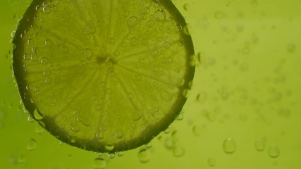 lime in soda water on green background