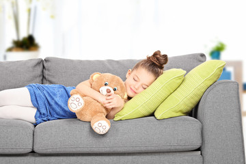 Little girl sleeping on couch with teddy bear