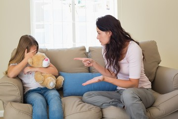 Woman pointing at scared daughter on sofa