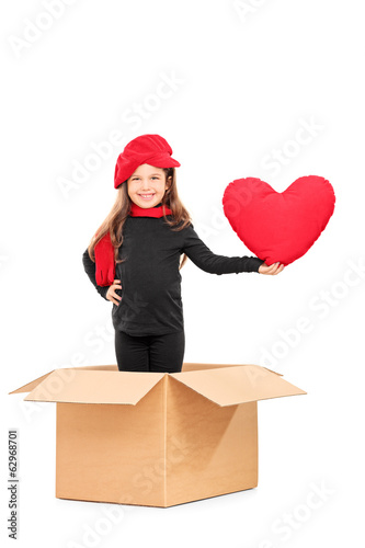 Little girl standing in a box and holding a red heart