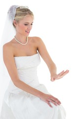 Bride looking at wedding ring over white background