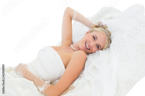 Happy sensuous bride lying against white background