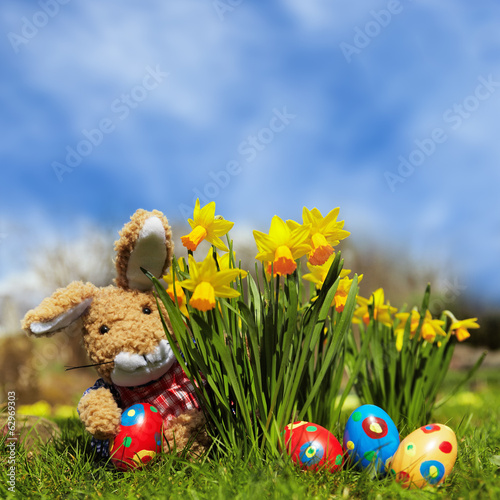 stuffed Easter bunny, daffodils and painted Easter eggs