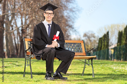 Male student posing with diploma  in park