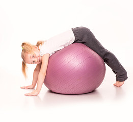 Sportive girl on a fit ball isolated over white
