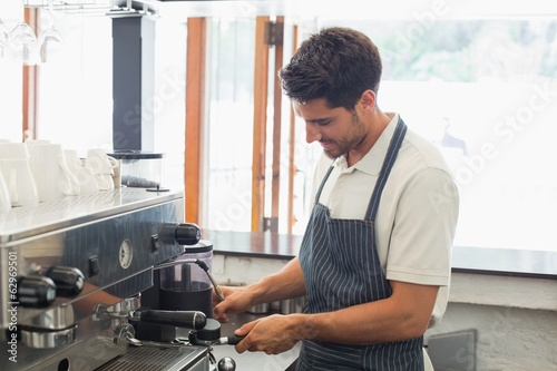 Smiling barista preparing espresso at coffee shop