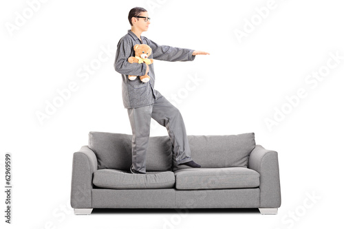 Man in pajamas sleepwalking on sofa