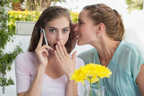 Woman whispering secret into friends ear while shes on call