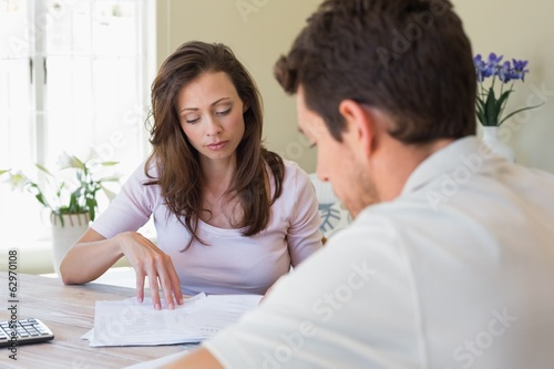 Young couple sitting with home bills at table