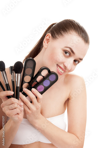 Beautiful smiling woman with set of brushes and palette of color