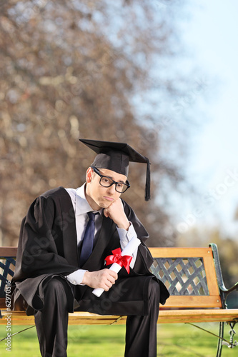 Worried graduate student sitting on a bench in park