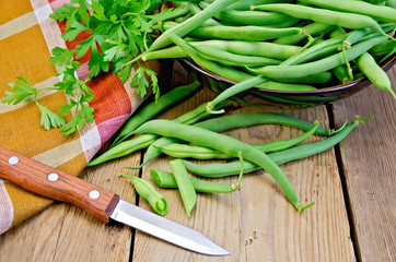 Beans green on board with knife and napkin