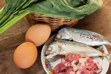 Fish, pork, eggs and kale on a wooden floor.