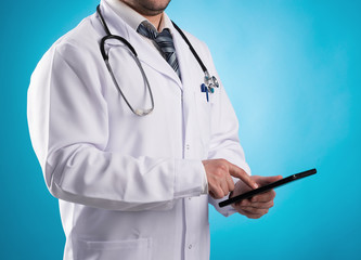 Men doctor physiotherapist holding digital tablet at his office