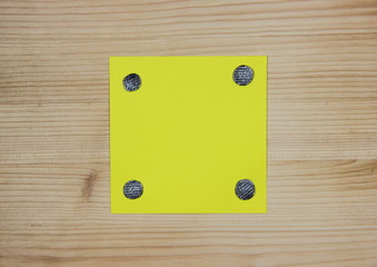Yellow note attached to wood with nails