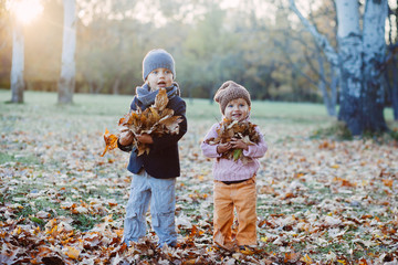 brother and sister playing in autumn park leaves