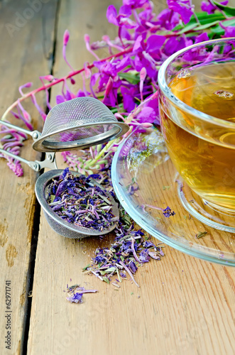 Herbal tea in cup of fireweed with a strainer on board