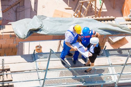 Team bespricht Bau Pläne auf einer Baustelle