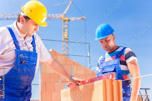 Zwei Handwerker kontrollieren Wände auf Baustelle