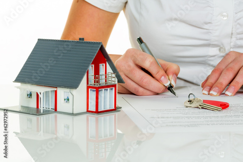 Frau unterschreibt Kaufvertrag für Haus