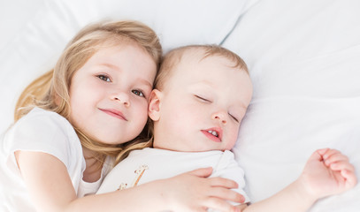 cute little girl hugs a sleeping baby brother