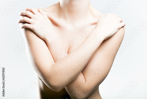 Woman covering her breasts arms
