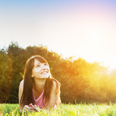 Young beautiful woman smiling and lying on the grass