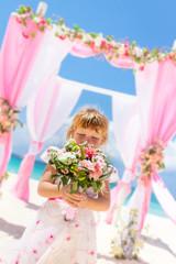 young happy kid girl in beautiful dress on tropical wedding setu