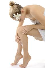 Frau cramt Bein mit Hautcreme ein