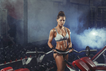 Young sexy woman training with barbell in the gym with smoke