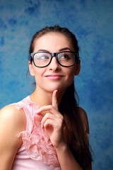 Thinking cute woman in glasses looking on blue background