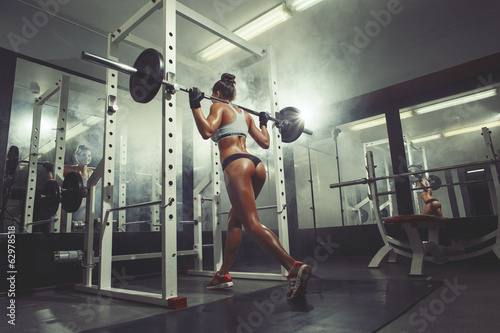Fototapeta Young sexy girl in the gym doing squat on smoke background