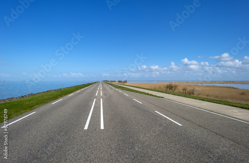 Road on a dike along a lake in spring - 62978749