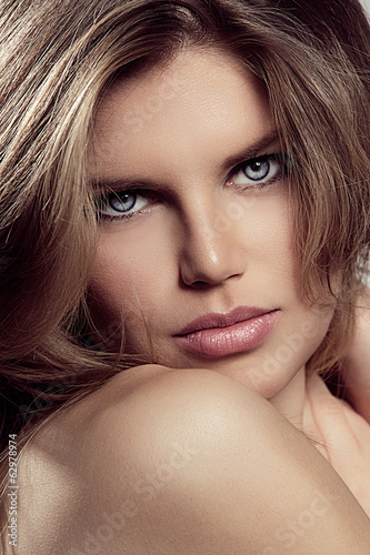 Portrait of blond model with blue eyes and luxuriant hair