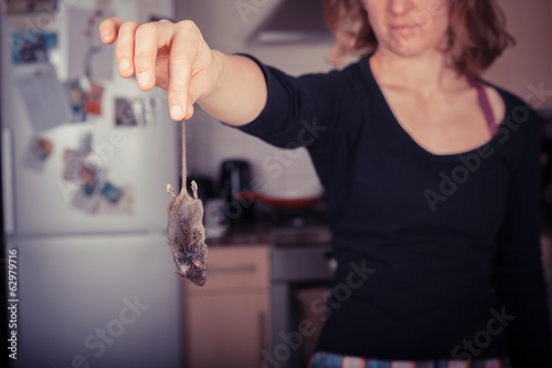 Woman holding a dead mouse in her kitchen