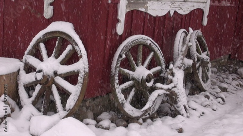 wheels near farm house and winter snow falling