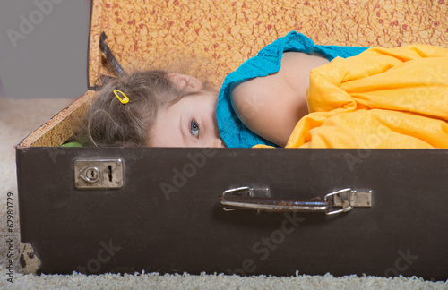 Dreaming little girl lying in an old suitcase