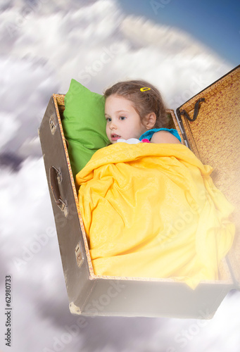 Dreaming girl flying in the cloudy sky in an old suitcase
