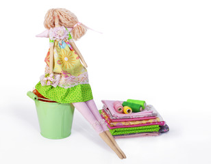 Handmade doll sits, all for sewing, isolated on white