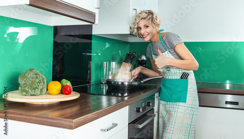 Young woman cook or housewife gesturing thumbs up