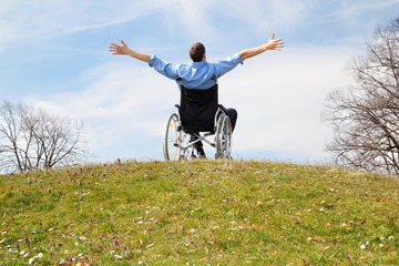Rollstuhlfahrer gluecklich auf gruenem Huegel