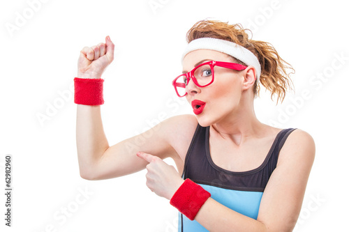 Funny fitness woman pointing on her biceps